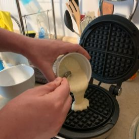 Pouring waffle batter made with sourdough starter discard
