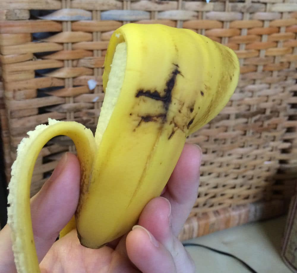 Brown area on a banana, just below a dark impact wound on its peel